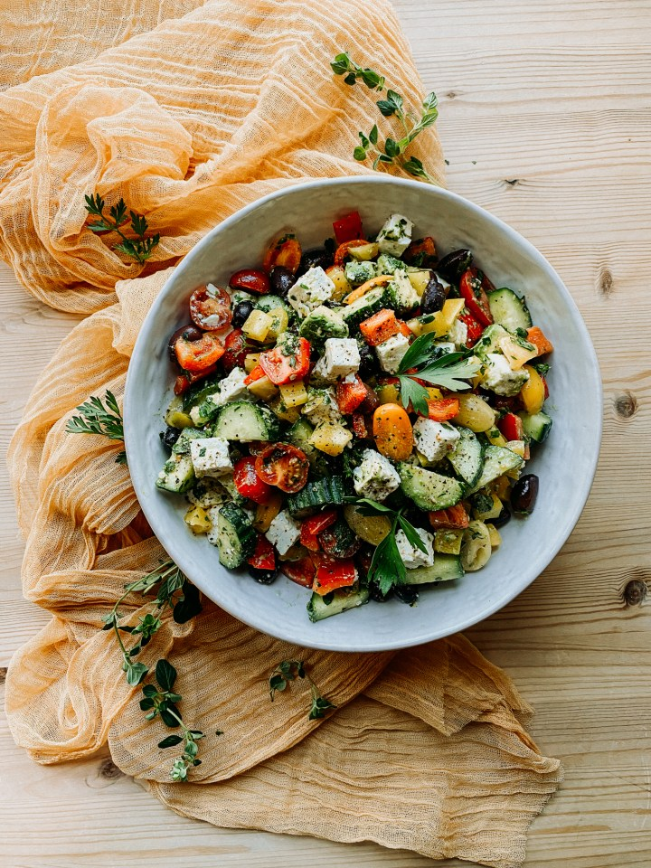 a big bowl filled with Crunchy Greek Salad on a piece of golden gauze over a wooden table