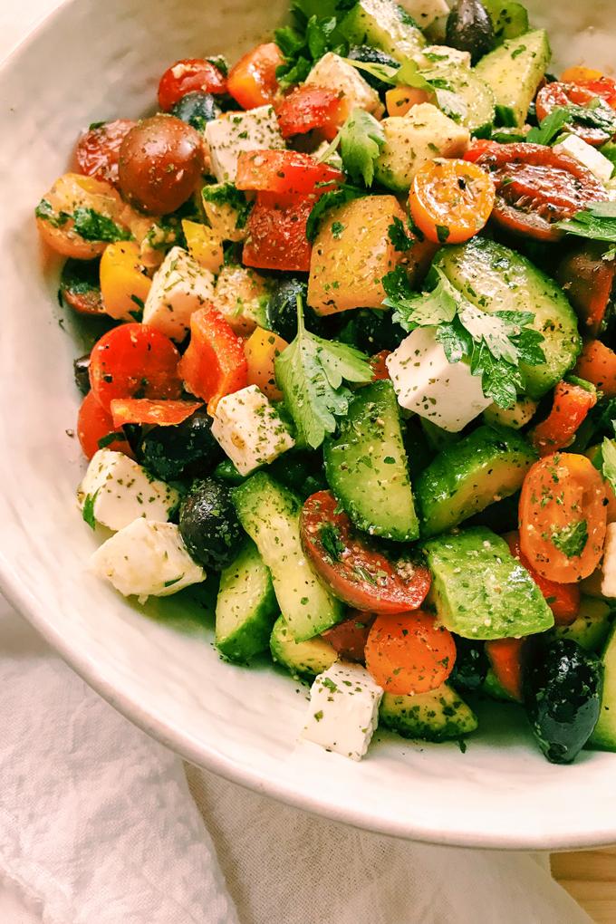 closeup of crunchy greek salad with avocado and feta