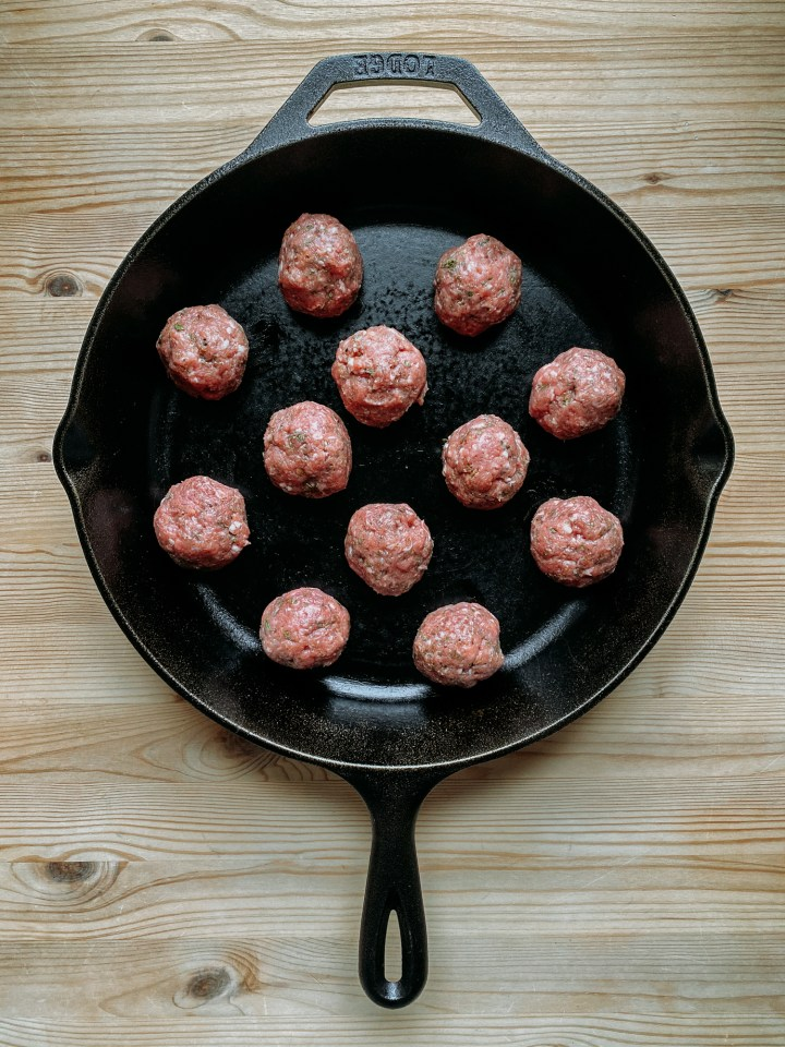 a cast iron pan filled with raw lamb meatballs resting on a wooden table
