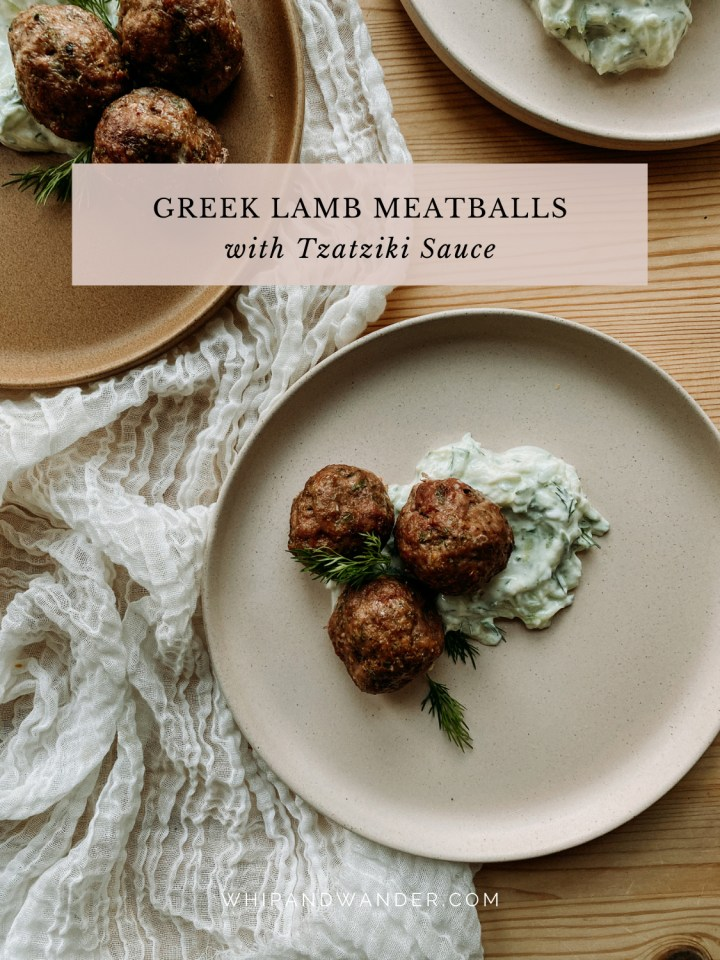 a pink plate containing 3 Greek Lamb Meatballs with Tzatziki Sauce and dill next to a brown plate on a white fabric cloth
