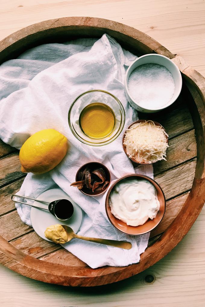 a wooden tray with caesar dressing ingredients, lemon, parmesan, yogurt, garlic oil, Dijon, anchovies