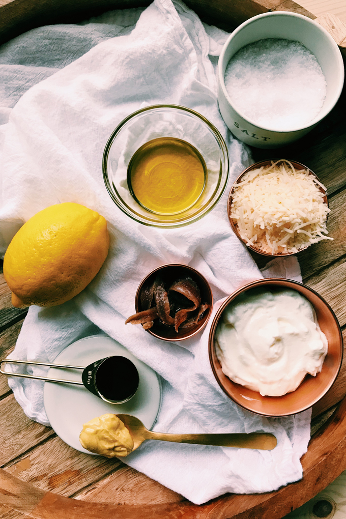 lemon, yogurt, anchovies, parmesan, garlic oil, mustard in prep bowls on a white towel