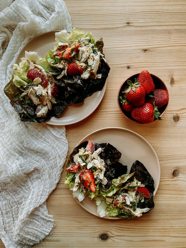 two brown plates with butter lettuce and Strawberry Poppy Seed Chicken Salad and a copper bowl filled with strawberries on a wooden surface