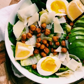 Jammy eggs, chickpeas, avocado, parmesan salad in white bowl