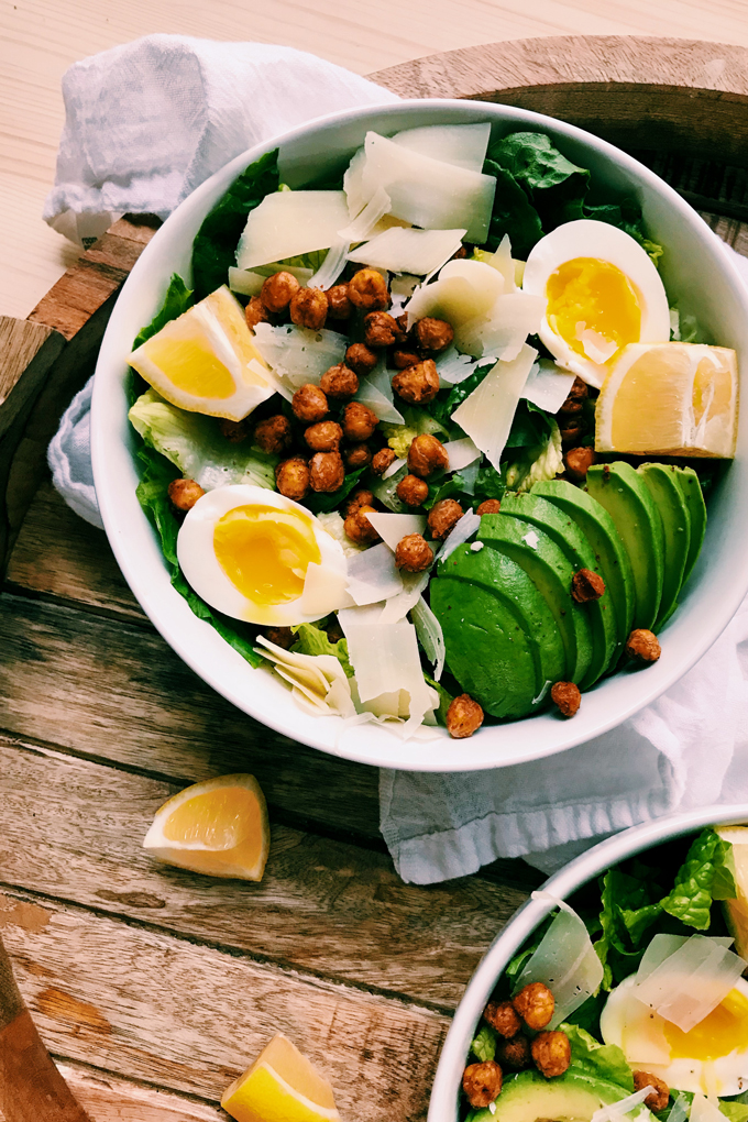 caesar salad with chickpeas and avocado, lemon, jammy eggs, cheese in a white bowl on a wooden surface