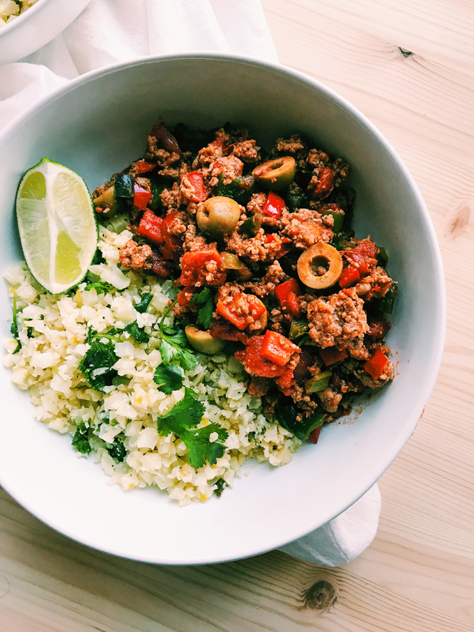 Cuban Picadillo in a white bowl with cauliflower rice and lime