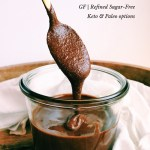 a gold spoon with nutella dripping off the end into a glass jar