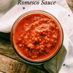 romesco sauce in a glass jar with a tea towel on a wooden surface