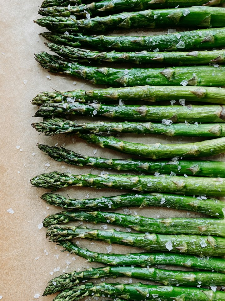 flaky salt topped broiled asparagus stalks on a baking sheet
