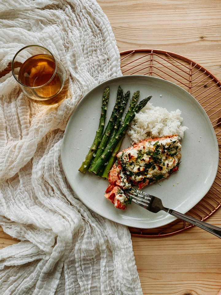 petunia dursley's fancy roasted salmon on a pate with asparagus, rice, and a fork restin on a copper tray with a white cloth and a glass of wine next to the plate