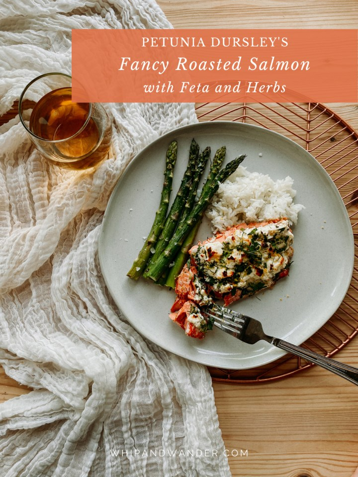 a white plate with Petunia Dursley's Roasted Salmon with Feta and Herbs, asparagus, rice and a fork on a white cloth lined copper tray with a glass of wine to the left