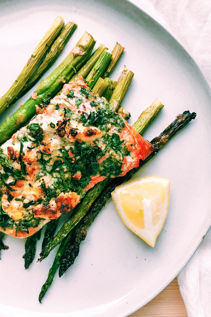 salmon with herbs and cheese over asparagus on a white plate with a wedge of lemon next to it