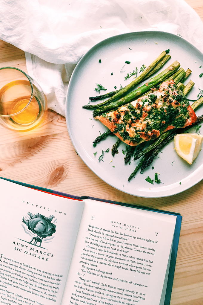 a white plate with asparagus, salmon with feta and herbs, a glass of wine and a harry potter book