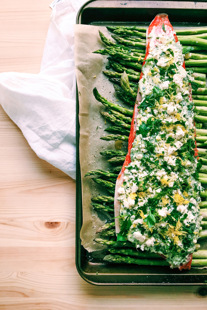 a baking tray with asparagus and salmon with feta and herbs on a white towel