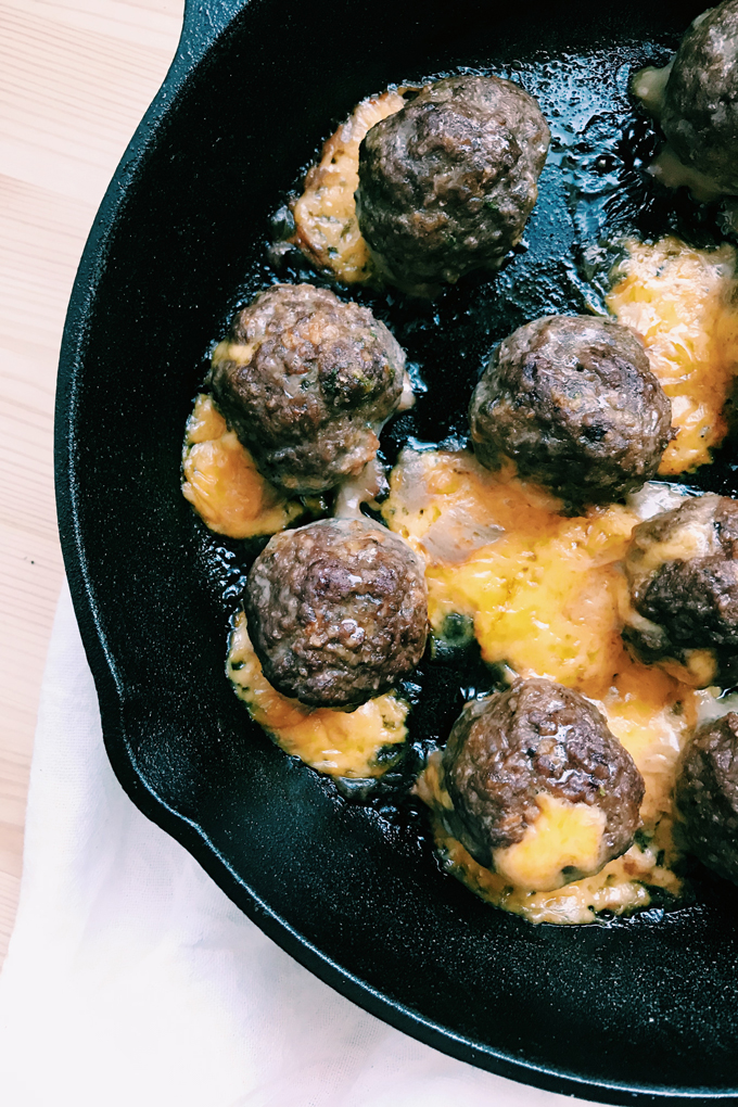 baked meatballs with cheddar cheese seeping out of them