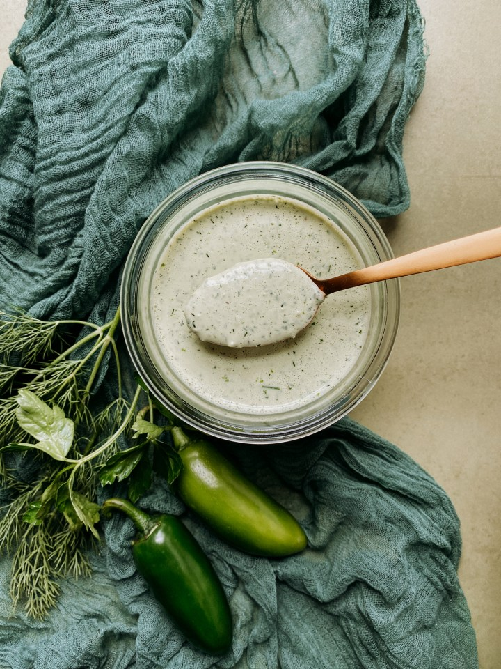 a gold spoon holding a spoonful of Buttermilk Jalapeno Ranch Dressing over the top of a glass container with a green cloth underneath