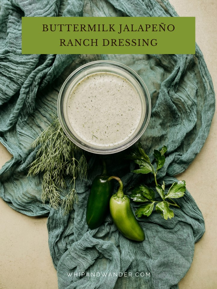 a glass jar of Buttermilk Jalapeno Ranch Dressing resting on a green cloth with herbs and fresh jalapenos