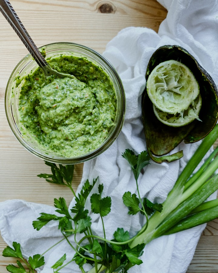 creamy avocado chimichurri sauce ina glass jar with limes, avocado, and green onion resting on a towel nearby