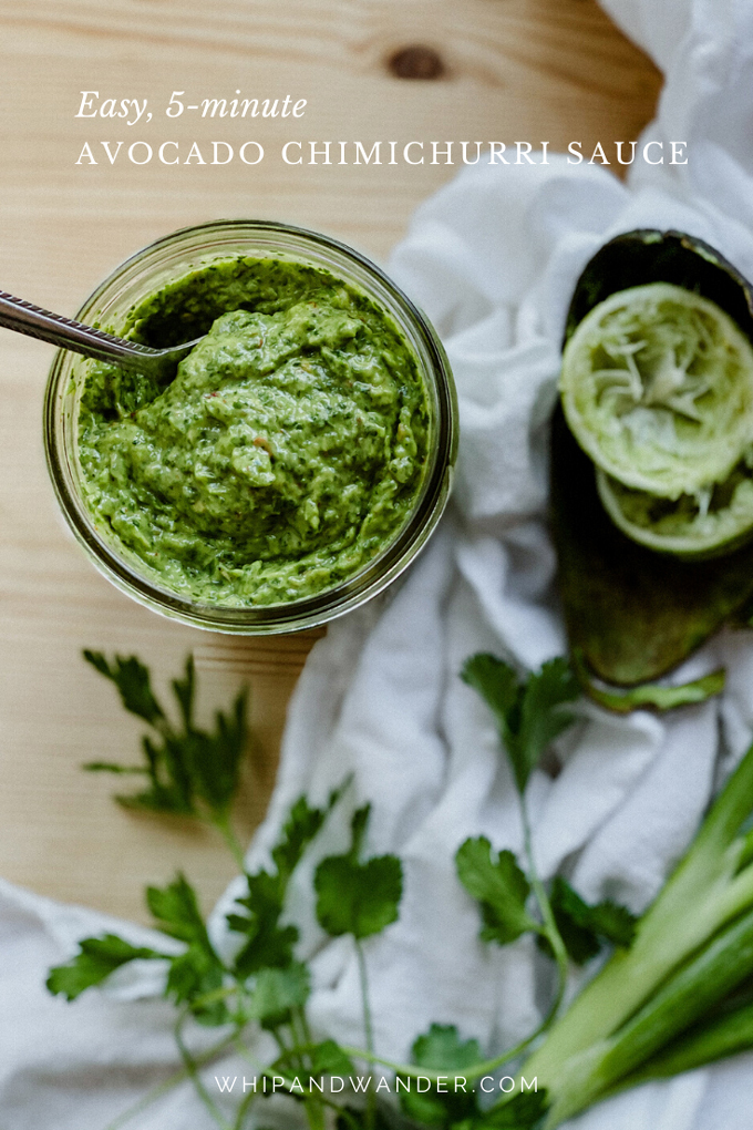 a spoon dipping into Avocado Chimichurri Sauce in a glass jar with the green herbs and fruits that go into making the sauce resting nearby