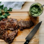 a wooden cutting board with grilled skirt steak with a green citrus herb sauce in a glass jar next to it and a chef's knife resting on the board