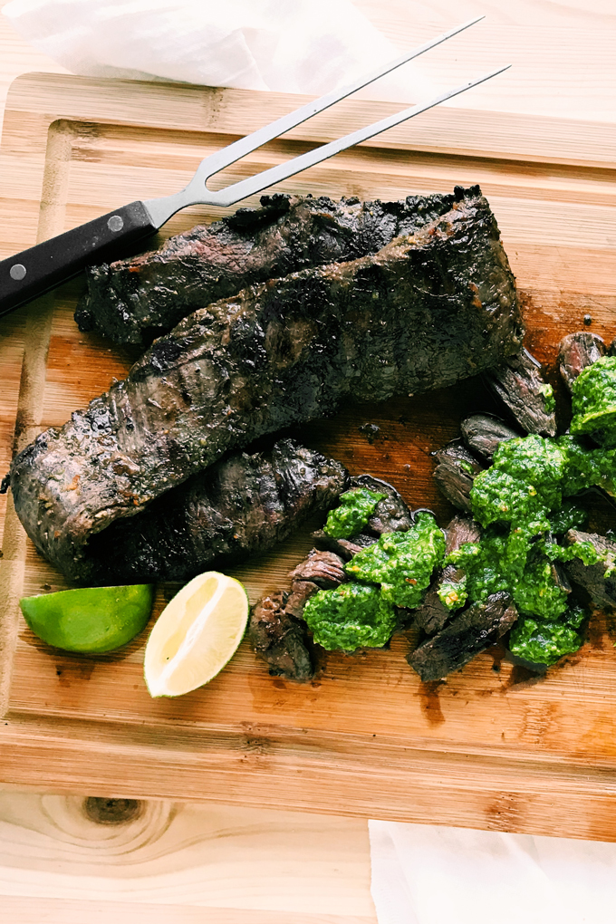 a bamboo cutting board with grilled skirt steak and green chimichurri sauce
