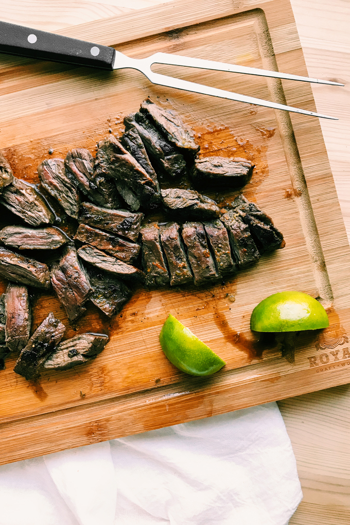 sliced skirt steak on a cutting board with limes