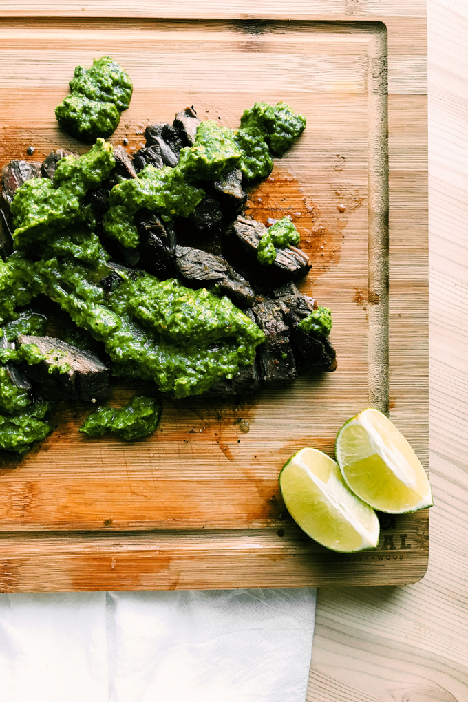 slices of steak with avocado chimichurri and limes