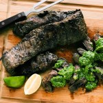 Grilled skirt steak with avocado chimichurri sauce and lime on a bamboo cutting board