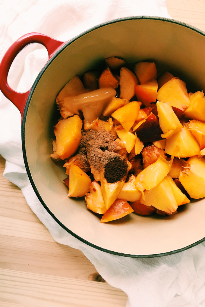 a pot filled with diced peaches, honey, and spices