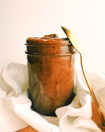 a glass jar of peach butter with a gold spoon resting on the right side