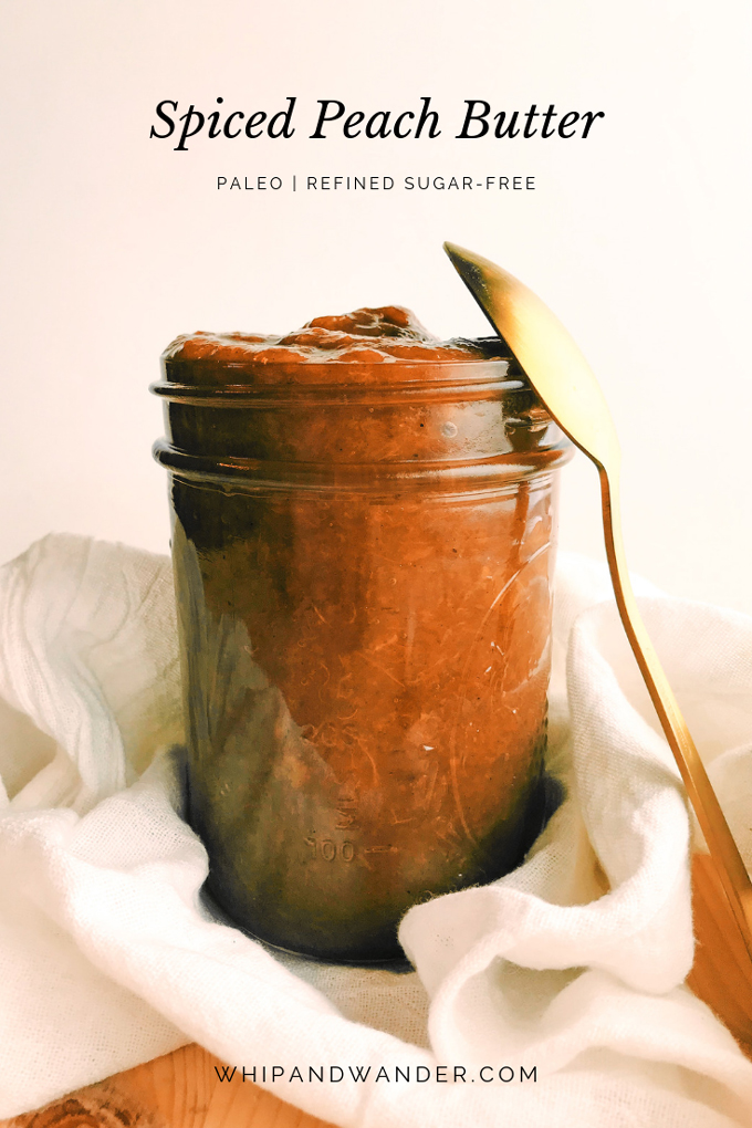 a gold spoon resting on a glass jar of spiced peach butter