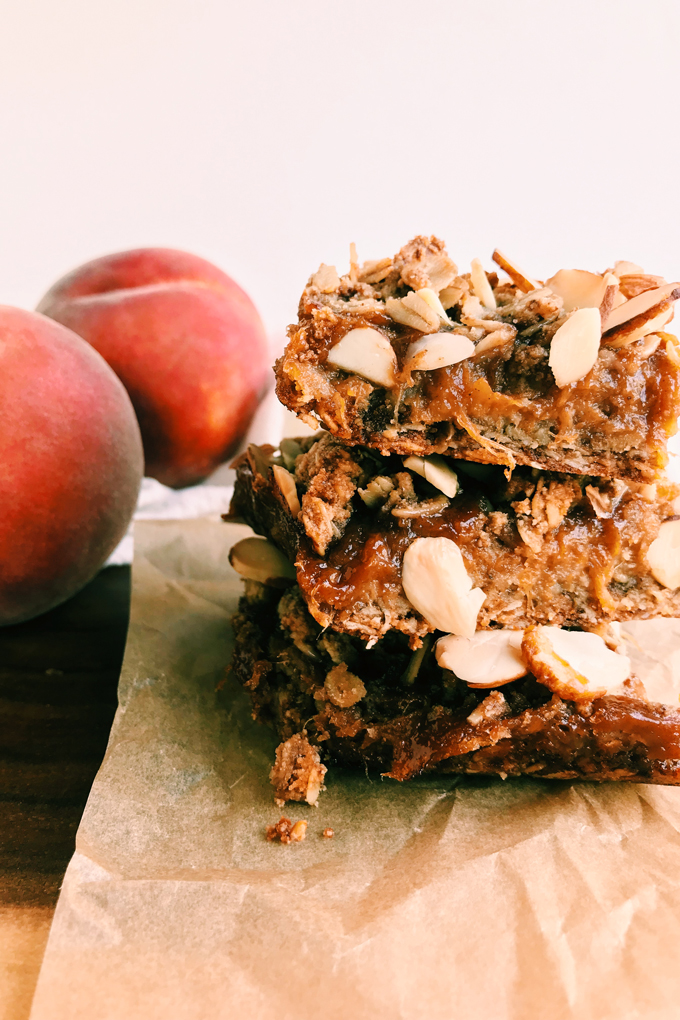a stack of 3 spiced peach crumble bars next to two fresh peaches