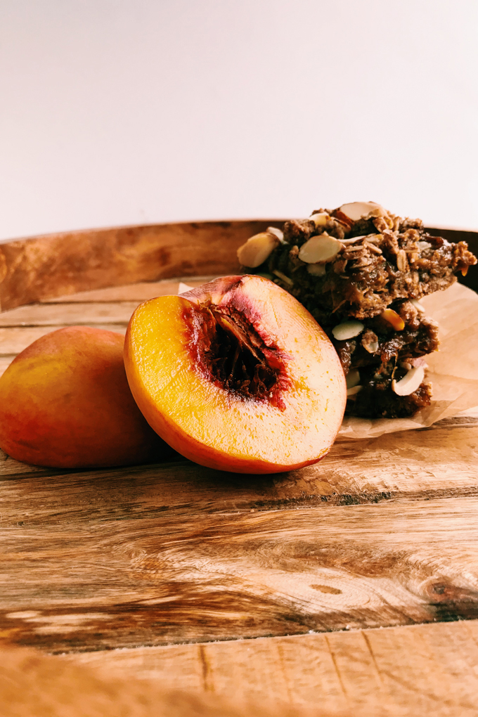 a sliced peach sitting next to spiced peach crumble bars on a wooden tray