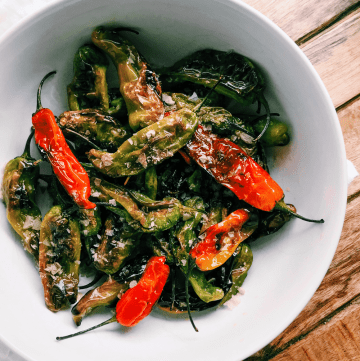 Blistered Shishito Peppers in a white bowl with flaky smoked salt on a wooden tray