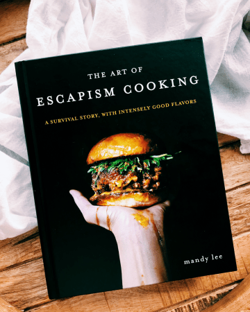 The Art of Escapism Cooking cookbook on a white towel laden wood tray