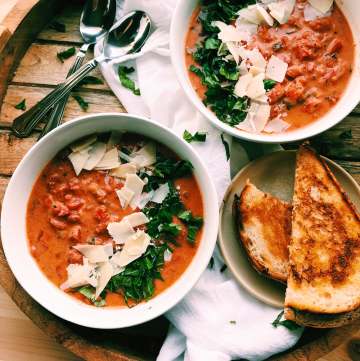 a wood tray with tomato soup and grilled cheese sandwiches