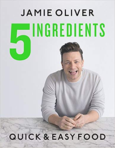 jamie oliver sitting at a table smiling on a gray background with green text