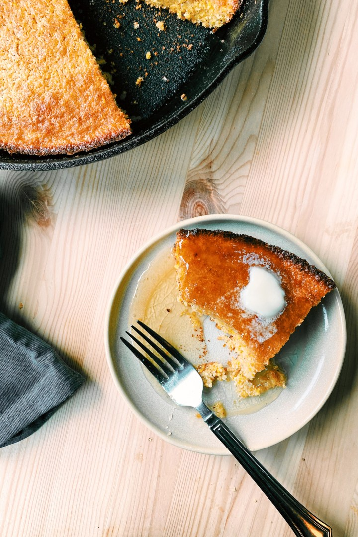 a slice of Brown Butter Buttermilk Skillet Cornbread resting on a plate with a fork and a cast iron pan in the background