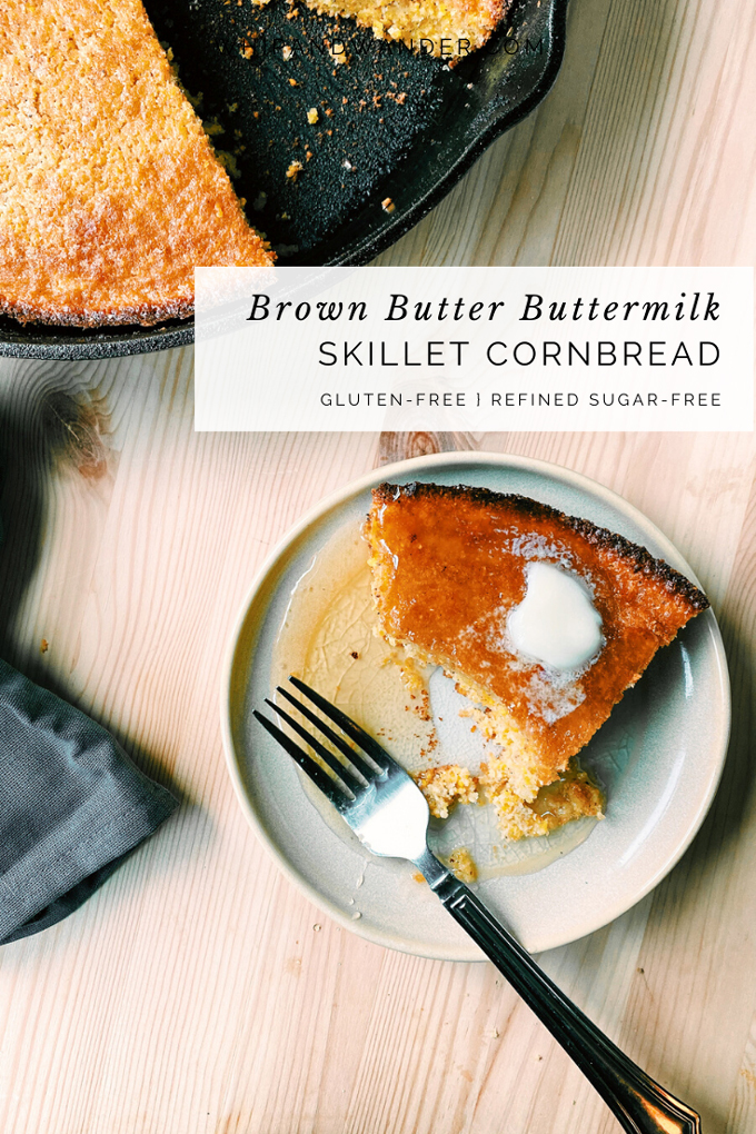 a partially eaten piece of Brown Butter Buttermilk Skillet Cornbread resting on a honey drenched tan plate and a fork