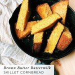 wedges of Brown Butter Buttermilk Skillet Cornbread stacked in a cast iron skillet resting on a white towel