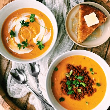 two bowls of Roasted Butternut Squash Soup with spoons resting nearby and a slice of cornbread topped with honey and butter on a tan plate