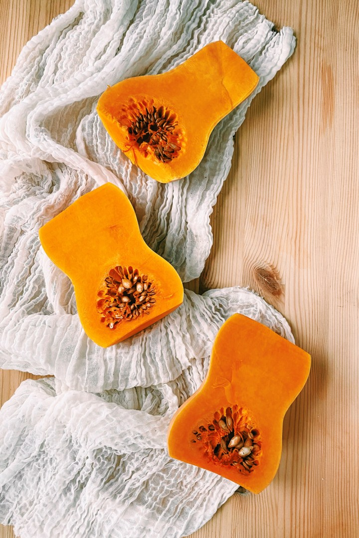 3 halves of raw butternut squash on a white cheese cloth resting on a wooden surface
