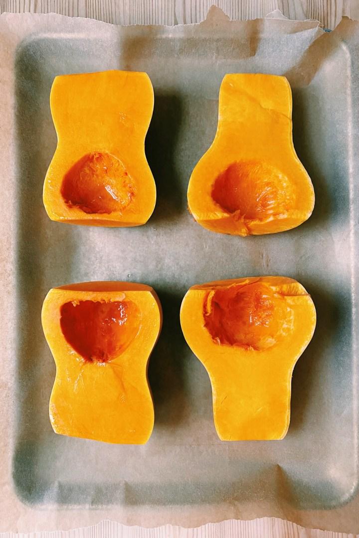 4 butternut squash halves on a parchment paper lined baking sheet