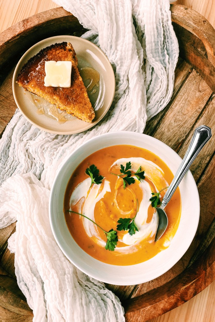 a spoon resting in a white bowl of roasted butternut squash soup with herbs on top and a plate of cornbread with honey and butter resting nearby