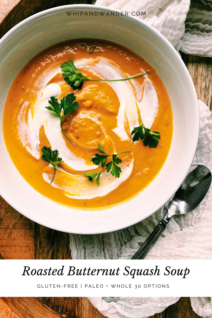 a closeup of a bowl of Roasted Butternut Squash Soup with herbs and sour cream and a silver spoon resting on a white towel