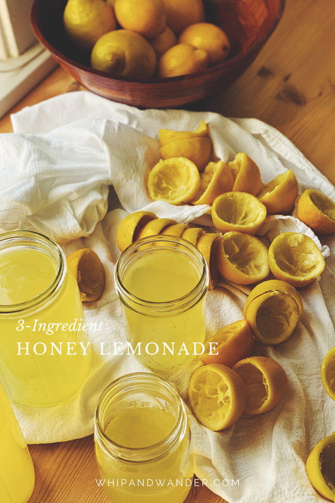several glass mason jars filled with hoeny lemonade, and lots of lemon halves nearby that have been juiced