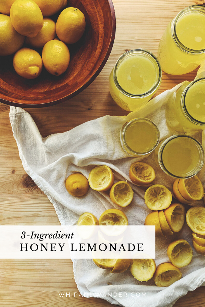 a bowl filled with whole lemons, a white towel with hlaves lemons that have been juice,a nd mason jars filled with honey lemonade