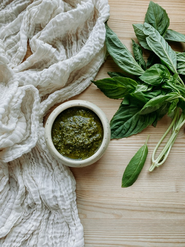a white cloth, a dish of basil walnut pesto sauce, and a bundle of fresh basil on a wooden surface