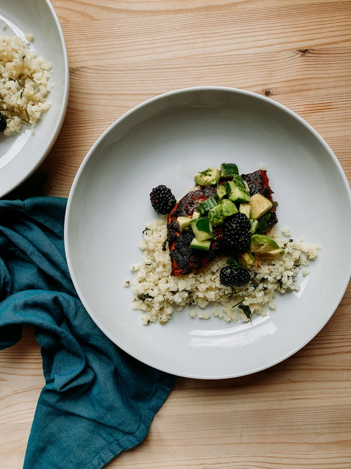 a white bowl containing cauliflower rice, cilantro, salmon with adobo sauce, and blackberry, cucumber, avocado salsa