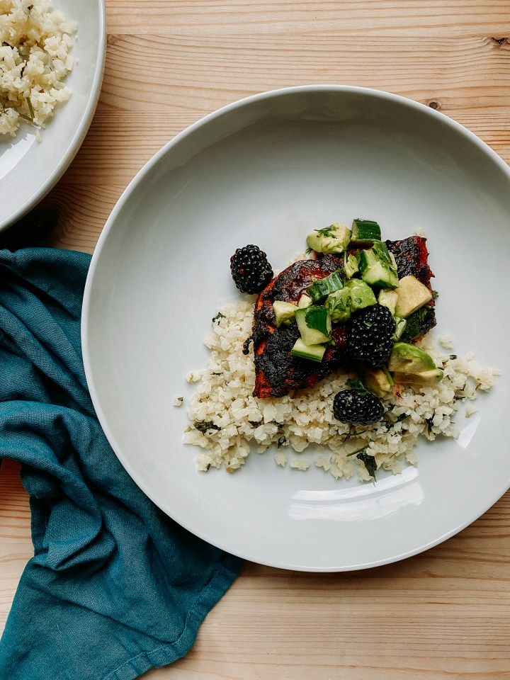 a white bowl with salmon with adobo sauce and cucumber, blackberry, and avocado salsa resting on top of a bed of cilantro lime cauliflower rice